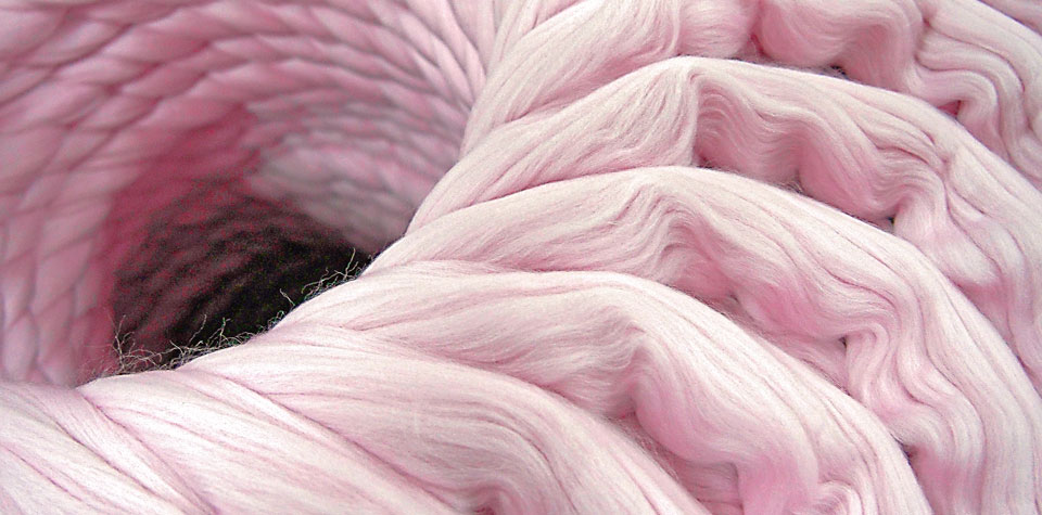 Pink-coloured wool ready to be spun into yarn and made into Pierre Robert wool tops for kids.